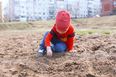 Little boy plays with sand outdoors Royalty Free Stock Photo