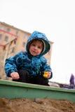 Little boy plays in a sandbox on playground Stock Image