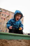 Little boy plays in a sandbox on playground Stock Photo