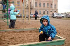 Little boy plays in a sandbox on playground Stock Images