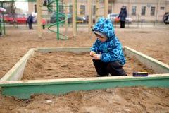 Little boy plays in a sandbox on playground Stock Photos