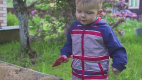 A little boy plays with a sandbox and wipes sand from the sneakers. A little boy plays with a sandbox and wipes sand from the sneakers stock video footage