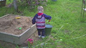 A little boy plays with a sandbox and wipes sand from the sneakers. A little boy plays with a sandbox and wipes sand from the sneakers stock footage