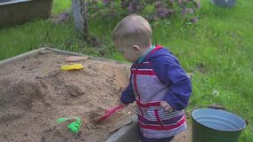 A little boy plays with a sandbox and wipes sand from the sneakers. A little boy plays with a sandbox and wipes sand from the sneakers stock video
