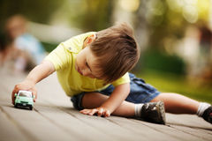 Little boy plays with toy car. In park royalty free stock photos
