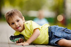 Little boy plays with toy car. In park Royalty Free Stock Images