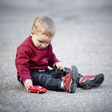 Little boy plays with toy car Stock Images