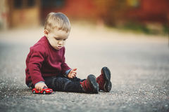 Little boy plays with toy car Stock Image