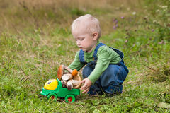 Little boy plays a toy car with mushrooms Royalty Free Stock Photography