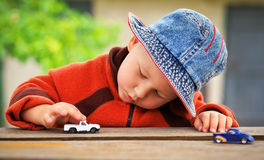 Little boy plays with toy cars. Stock Images