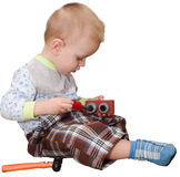 The little boy plays with a toy screw-driver. It is isolated on Stock Photos