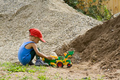 Little boy plays with a toy tractor. The little boy plays with a toy tractor about a heap of sand and rubble Royalty Free Stock Image