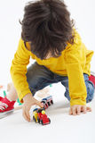Little boy plays with toy train near wooden railway Royalty Free Stock Photos