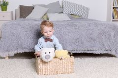Little boy plays with toys in basket in cozy bedroom. At home Royalty Free Stock Photos