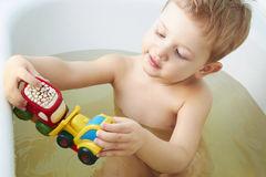 Little boy plays toys in bathroom Stock Image