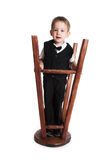 The little boy plays with the turned stool stock photo