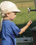 Little boy plays with water (1). A little boy in a blue sport shirt plays with water near a metallic barrel with a faucet on a background a rural meadow Royalty Free Stock Photo