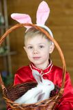 Little boy plays with white Easter Bunny. on the green grass and baby bunnies, Spring Festival and birth. Living Easter rabbits royalty free stock image