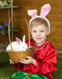 Little boy plays with white Easter Bunny. on the green grass and baby bunnies, Spring Festival and birth. Living Easter rabbits stock photos