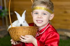 Little boy plays with white Easter Bunny. on the green grass and baby bunnies, Spring Festival and birth. Living Easter rabbits royalty free stock images