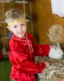 Little boy plays with white Easter Bunny. on the green grass and baby bunnies, Spring Festival and birth. Living Easter rabbits royalty free stock photos