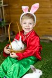Little boy plays with white Easter Bunny. on the green grass and baby bunnies, Spring Festival and birth. Living Easter rabbits stock photo