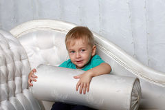 A little boy plays with a white pillow Royalty Free Stock Photography