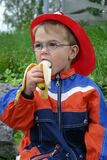 Little boy pleasurably bites into a banana