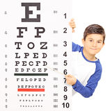 Little boy pointing on an eyesight test with stick. Isolated on white background, shot with tilt and shift lens Royalty Free Stock Image