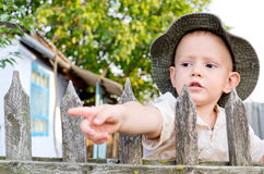 Little boy pointing through picket Stock Image
