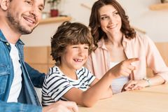 Little boy pointing somewhere with his family. Sitting besides Stock Photo