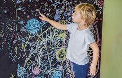 Little boy pointing space, planets and stars on the wall royalty free stock photo