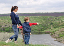 Little boy pointing to something in the country. Little boy pointing to something countryside showing his mother point  interest they stand together top grassy Stock Photo