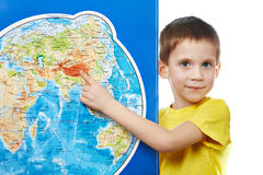 Little boy points to place on world map. Royalty Free Stock Images
