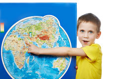Little boy points to place on world map. Royalty Free Stock Image