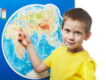 Little boy points to place on world map. Stock Photo