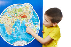 Little boy points to place on world map Royalty Free Stock Photo