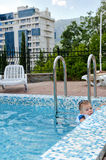 Little boy in a pool hanging onto the edge. Little boy swimming in a pool hanging onto the tiled edge as he enjoys the cool water while waiting for his mother to Stock Images