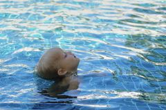 Little boy in pool learns to swim. Blonde hair head on surface, body is immersed water. Sunlight, clear blue water Royalty Free Stock Image