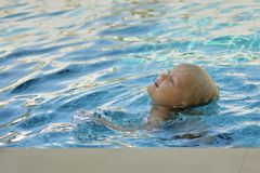 Little boy in pool learns to swim. Blonde hair head on surface, body is immersed water. Sunlight, clear blue water Stock Image