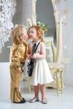 Little boy in pop retro suit kisses a girl Stock Photo