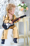 Little boy in pop retro suit playing the guitar Stock Photos