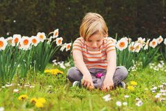 Little boy portrait. Adorable little blond boy playing with colorful easter eggs in the park, egg hunt stock photos