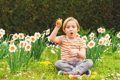 Little boy portrait. Adorable little blond boy playing with colorful easter eggs in the park, egg hunt royalty free stock photography