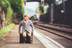 Little boy portrait. Adorable little boy on a railway station, waiting for the train with suitcase stock photos