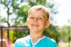 Little boy portrait with big smile outside. Close portrait of the little Caucasian happy boy in blue outside in the park with big toothy smile Stock Photo