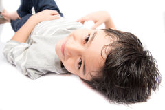 Little boy pose portrait lay on the floor on white. Little boy pose portrait lay on the floor Royalty Free Stock Photos