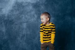 A little boy poses in front of a gray-blue concrete wall. Portrait of a smiling child dressed in a black and yellow striped stock photography