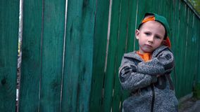 Cool boy changes facial expressions, child posing on camera near old wooden