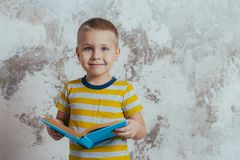 A little boy is smiling and holding a blue open book posing in front of a gray concrete wall royalty free stock photo